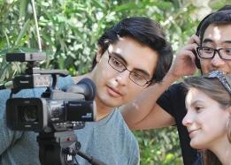 Three students looking into a film camera