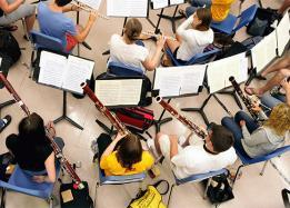 Students in classroom playing musical instrument, orchestra