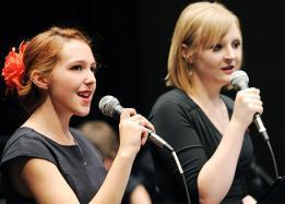 Two voice performance students singing to microphone
