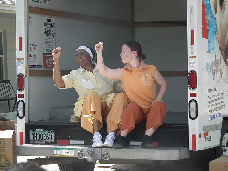 mobile theatre performance - two actresses sitting down in the back of an open shipping truck