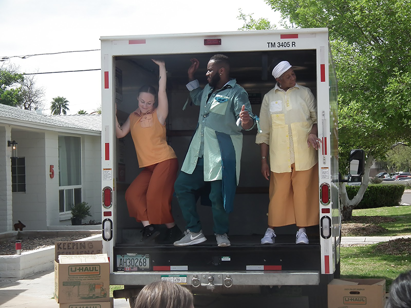 three performers dancing in the back of an open shipping truck