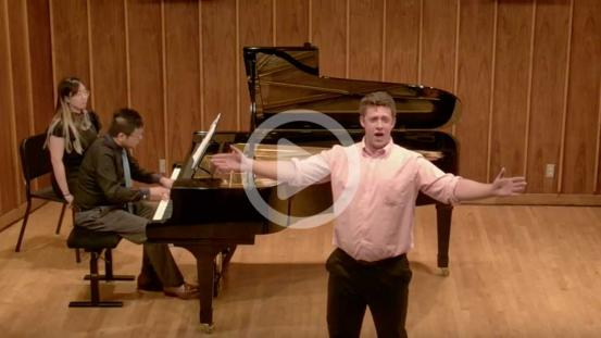 man singing in front of piano