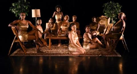 Women on a dimly lit stage wearing golden tops and bottoms
