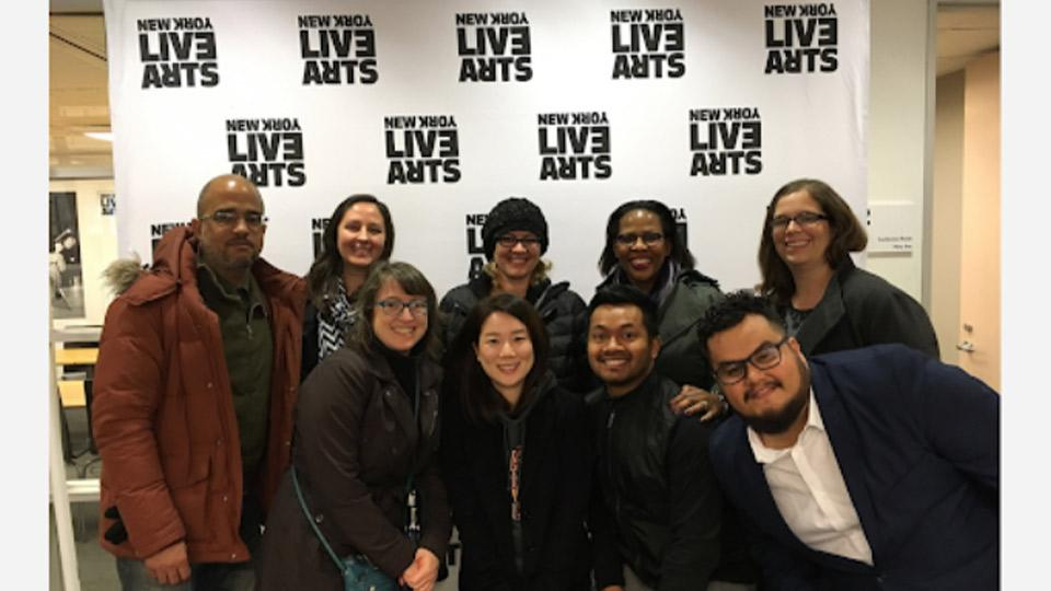 "A group posing for a picture in front of a ""Live Arts"" background."