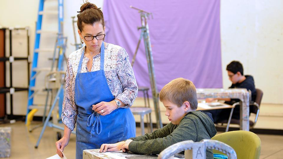School of Art teacher assisting schoolboy in the Children's Art Workshop
