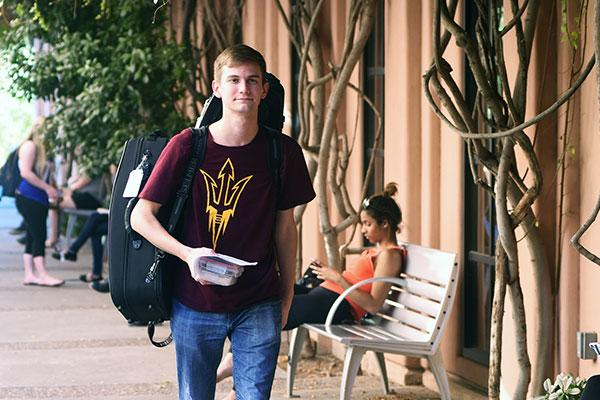 ASU Music student carrying instrument to class