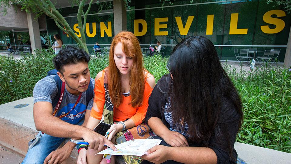 three freshman students reviewing the next steps after admission to ASU