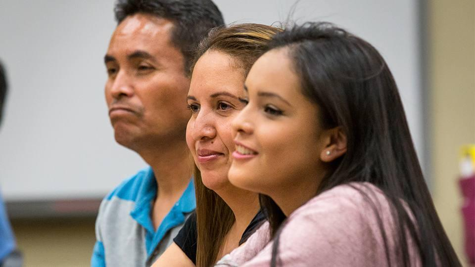 Latino parents and student learning about college requirements
