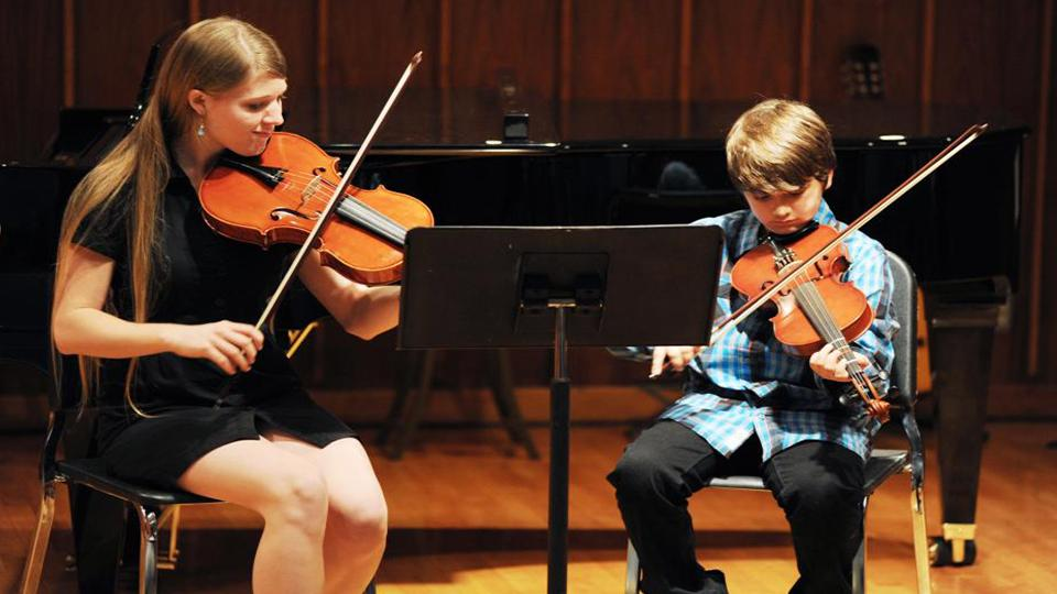 Teacher and young student playing with violins