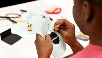 student sewing on a pattern