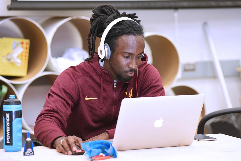 student with headphones working on laptop