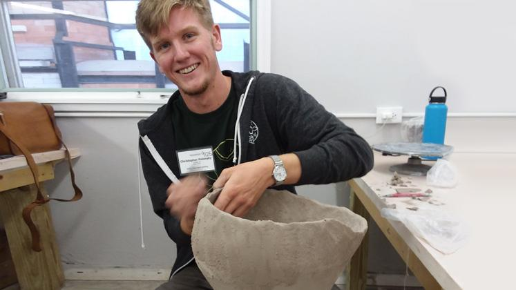 male student building a bowl out of clay