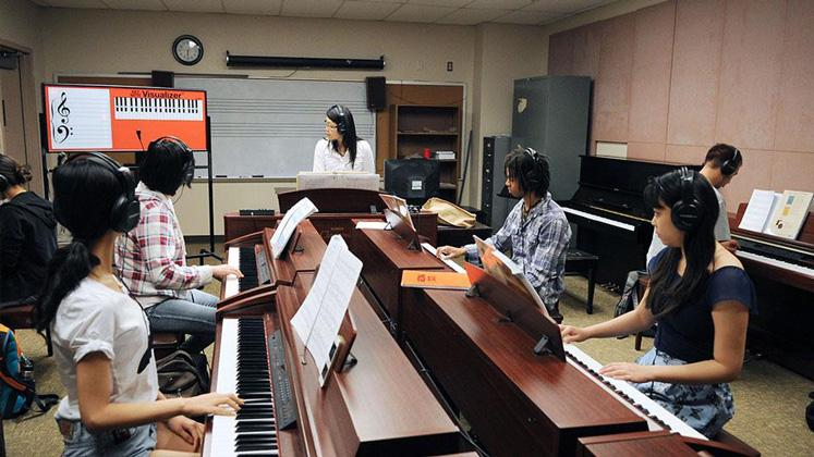 Amy Chou teaching, with a group of students each sitting at a piano