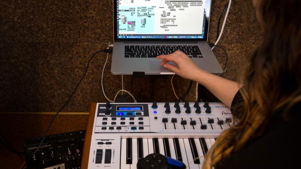 Student creating music on a computer with piano keyboard