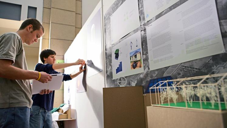 two students hanging landscape architecture posters