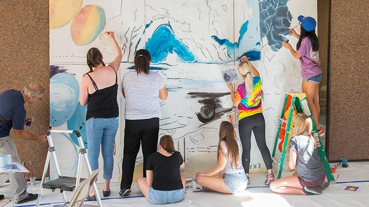 students working together on a large scale mural